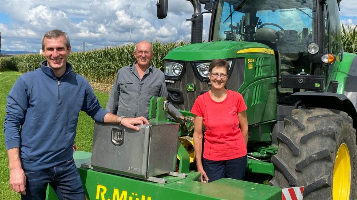 Raphael Müller posiert mit seinen Eltern Christian und Vreny vor dem Traktor